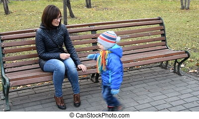 Young mother and naughty child in the park