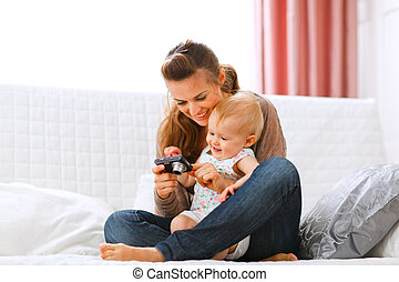 Young mother and smiling baby looking photos in camera