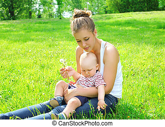Young mother and son child sitting on the grass in summer day
