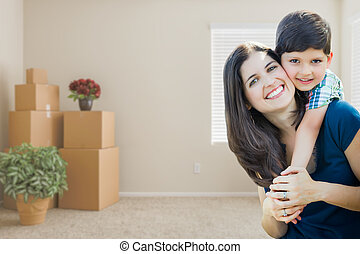 Young Mother and Son Inside Empty Room with Moving Boxes.