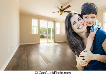 Young Mother and Son Inside Empty Room with Wood Floors.