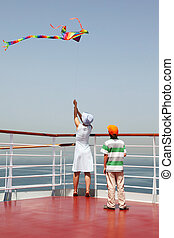 young mother and son playing with multicolored kite, standing on cruise liner deck