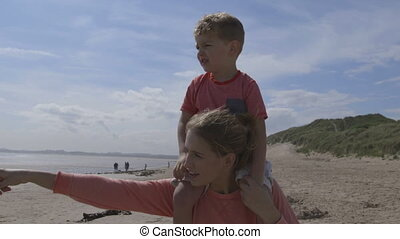 Young mother and son walking along the beach