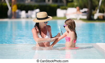 Young mother applying sun cream to daughter nose - Young...