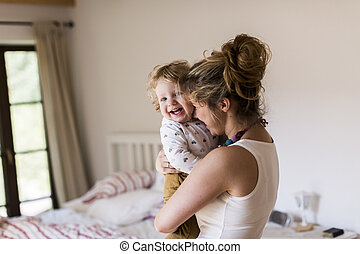 Young mother at home holding her cute little son - Beautiful...