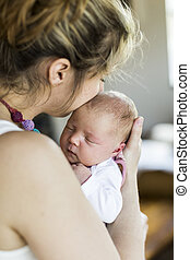 Young mother at home holding her newborn baby daughter -...
