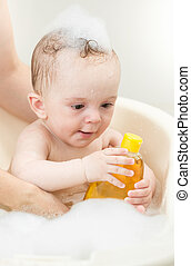Young mother bathing her baby boy in bath