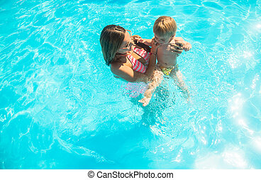 Young mother bathing in the pool with your child