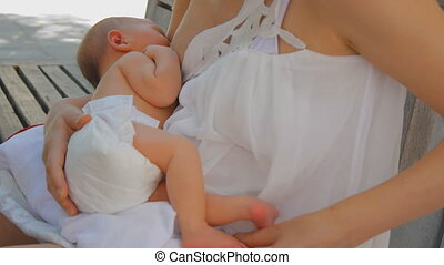 Young mother breastfeeding newborn baby girl