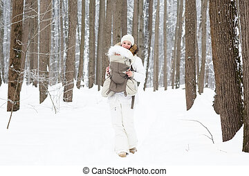 Young mother carrying her baby in the forest on a very snowy...