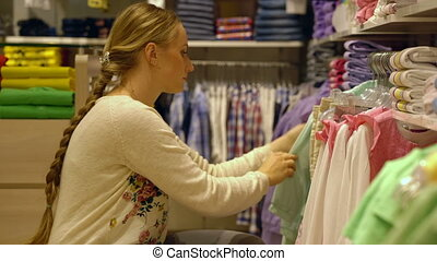 young mother chooses baby clothes in shop, portret