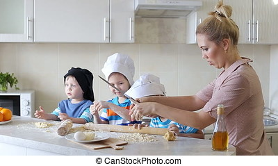young mother cooking in the kitchen with the children....