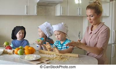 Young mother cooking in the kitchen with the children. Family having fun and preparing a meal.