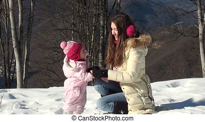 young mother dresses her daughter gloves