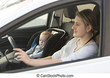 Young mother driving car with her baby boy sitting in car in baby seat
