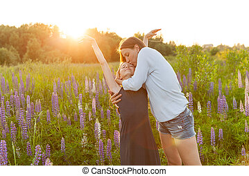 Young mother embracing her child outdoor. Woman and teenage girl on summer field with blooming wild flowers green background. Happy family mom and daughter playing on meadow.