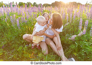 Young mother embracing her kids outdoor. Woman baby child and teenage girl sitting on summer field with blooming wild flowers green background. Happy family mom and daughters playing on meadow.