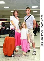 young mother, father and little daughter with baggage at the airport