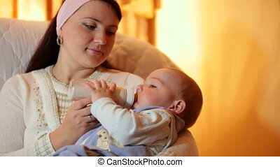 Young mother feeding baby boy milk formula from a bottle in the living room