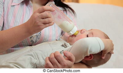 Young mother feeding her baby boy milk formula from a bottle in the living room