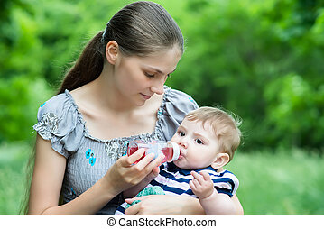 Young mother feeds her baby with a bottle