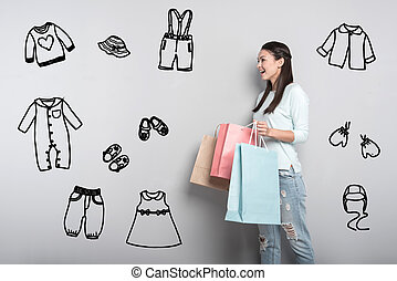 Young mother feeling impressed while buying clothes for her baby