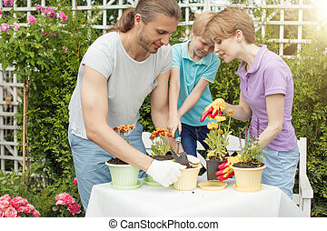 Young mother gardening in front or back yard with her two cute little children
