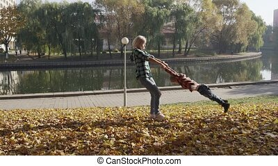 Young mother having fun with her son in autumn park at sunny day