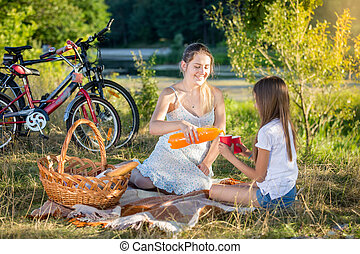 Young mother having picnic by the river with daughter. Mother pouring orange juice in daughter's cup