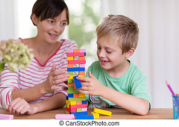 Young mother helping her son build a tower