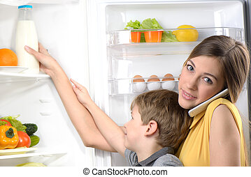 Young mother helping her son to get milk from fridge - Young...