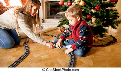 Young mother helping little son building tailways for toy train under Christmas tree at living room. Child receiving presents and toy on New Year or Xmas