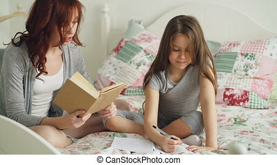 Young mother helps her little cute daughter with homework...