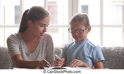 Young mother helps with school task to little daughter -...