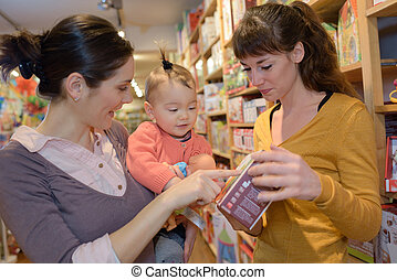 young mother her daughter in the toy store
