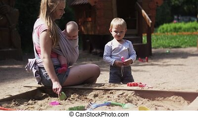 Young mother hold baby in sling, play with son in sandbox. Motherhood. Sunny day