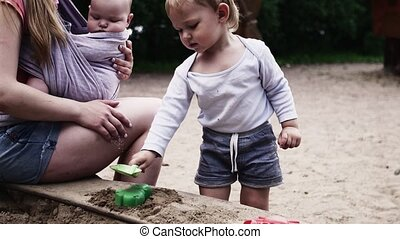 Young mother hold baby in sling play with son in sandbox on playground. Summer.