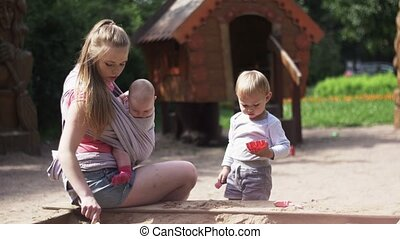 Young mother hold baby in sling, play with son in sandbox. Playground. Sunny day