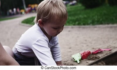 Young mother hold baby in sling play with son on playground in sand. Summer day