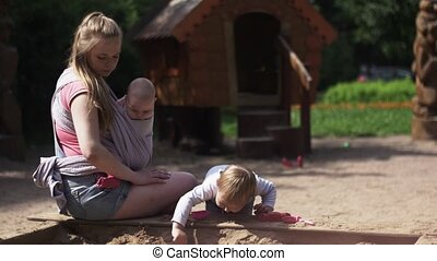 Young mother hold baby in sling, playing with son in sandbox. Playground.