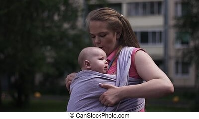 Young mother hold child in baby sling. Walking on street. Summer day. Motherhood