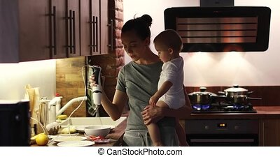 Young mother holding baby boy arms preparing food - Young...