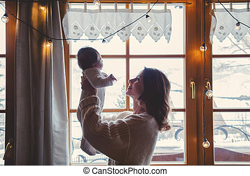 Young mother holding child indoor