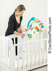 Young mother holding cute baby boy standing in white wooden cot