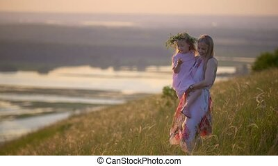 Young mother holding daughter in arms walks down the hill at...