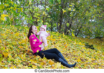 Young mother holding her baby catching falling autumn leaves