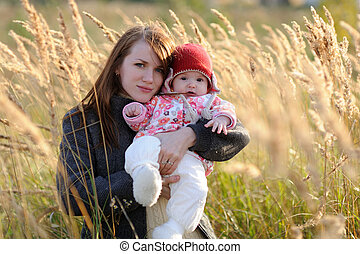 Young mother holding her baby in a meadow