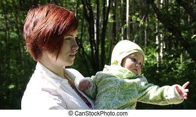Young mother holding her baby in the park