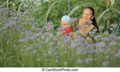 Young mother holding her newborn baby in a purple flower field