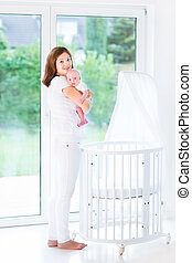 Young mother holding her newborn baby standing at a white crib n